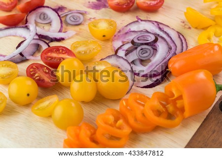 Close up of cutting board with cut vegetables: cherry tomatoes, bell peppers, red onion  - ingredients for salad. - stock photo