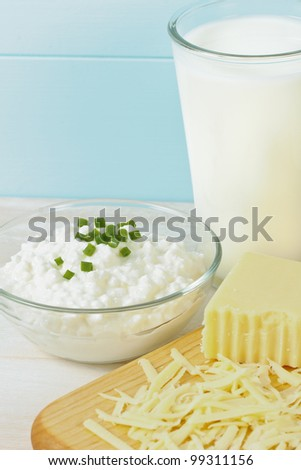 Close up of dairy products includes milk, cottage cheese and shredded Swiss cheese.