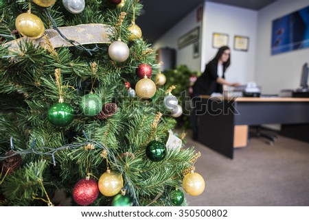 Close-up of decorated Christmas tree in office. Woman on background