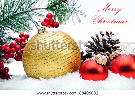 Close up of decorative Christmas balls, strobile, holly and Christmas tree on the snow. - stock photo