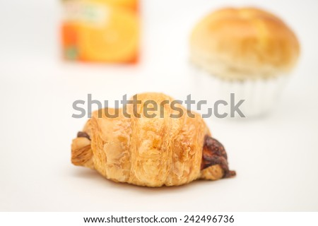 Close up of delicious and fresh baked croissant and bakery assortment with orange juice for break time - stock photo