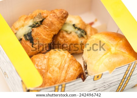 Close up of delicious and fresh baked croissant and soft bun in a paper box for take away breakfast - stock photo
