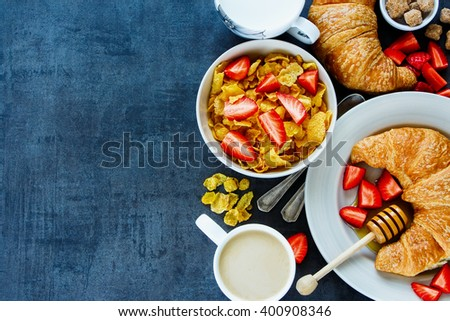 Close up of delicious breakfast table with corn flakes, fresh croissants, honey, ripe strawberry and coffee, border, top view. Health and diet concept. Vintage background with space for text. - stock photo