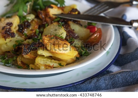 Close-up of delicious dish of friend slices of potato with onion and parsley