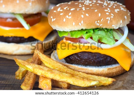 Close up of delicious homemade cheeseburger with fries. - stock photo