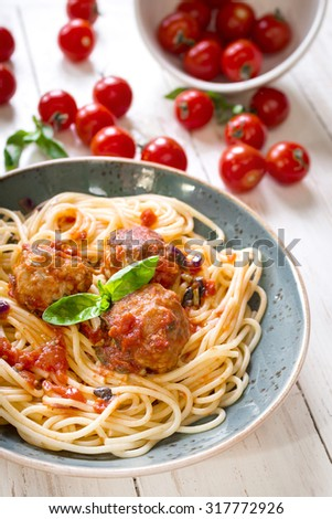 Close-up of delicious spaghetti with meatballs and tomato sauce on a plate. Serving on a white rustic wooden table. An Italian-American dish. Selective focus