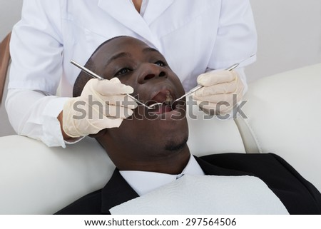 Close-up Of Dentist Hands Examining Teeth Of African Male Patient - stock photo