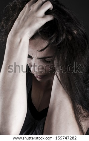 Close up of depressed woman holding hands on her head looking down - stock photo