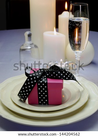 Close up of detail on wedding breakfast dining table setting with pink present gift with black polka dot ribbon on fina china with bell and candles.