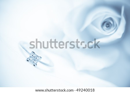 Close-up of diamond engagement ring with pink rose on background (shallow depth of field, blue toned image) - stock photo