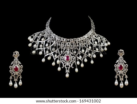 Close up of diamond necklace on black background with diamond ear ring - stock photo