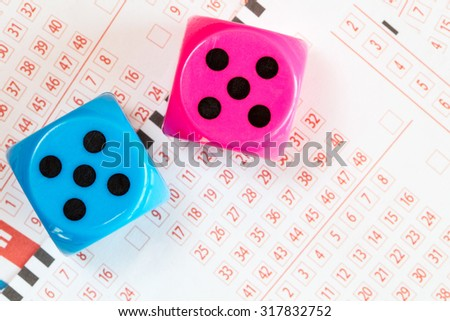 Close up of dice and lottery ticket - stock photo