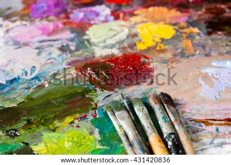 Close up of different paintbrushes on the bright multicolored palette of blended oil paints - stock photo