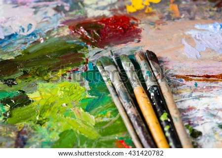 Close up of different professional paintbrushes on the bright multicolored palette of blended oil paints - stock photo