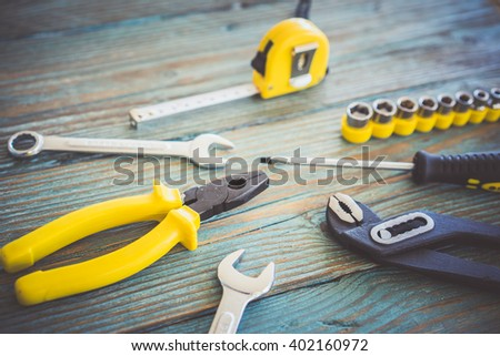 Close-up of different working tools on wooden table - stock photo