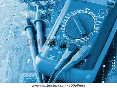 Close-up of digital multimeter on electronics circuit - stock photo