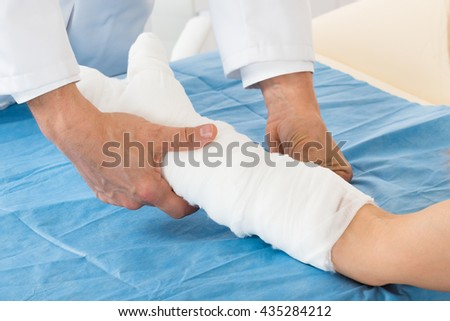 Close-up Of Doctor Bandaging Patient Hand In Hospital - stock photo