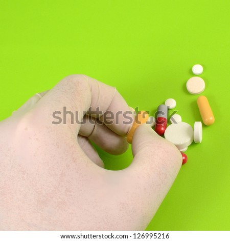 Close up of doctor hand taking pill - stock photo
