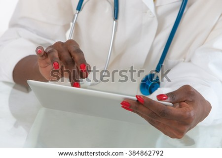 Close-up Of Doctor hans  on  Digital Tablet At Desk with stethoscope - stock photo
