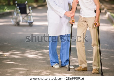 Close-up of doctor helping to his patient to walk with crutches. - stock photo