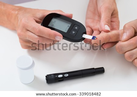 Close-up Of Doctor Measuring Sugar Reading Of Patient With Glucometer - stock photo