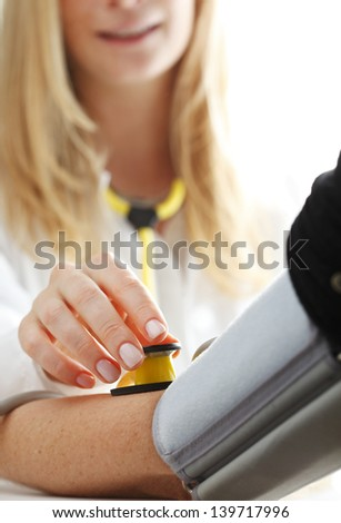 Close-up of Doctor/nurse checking blood pressure with stethoscope - stock photo