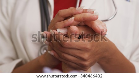 Close up of doctor's hands holding patient's hand - stock photo