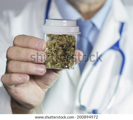 close up of Doctors hands holding medical marijuana - stock photo