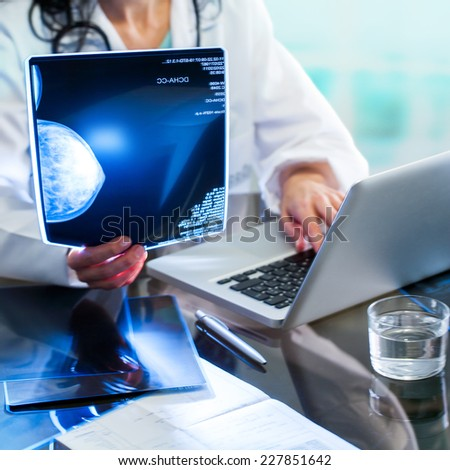Close up of Doctors hands reviewing x-ray of mammogram and introducing results on laptop. - stock photo