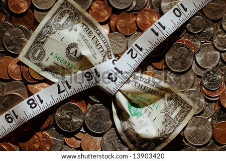 Close up of dollar being squeezed by measuring tape on top of coins. - stock photo