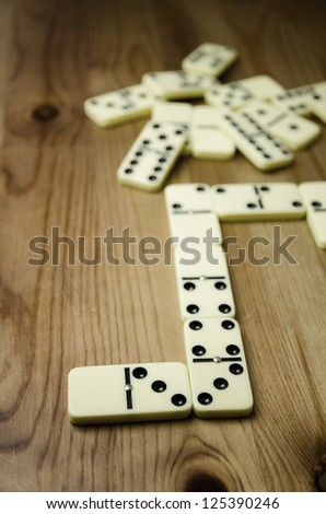 Close up of dominowith black dots on wooden background - stock photo