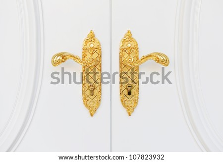 Close up of double antique gold plated door handle on the white door. - stock photo
