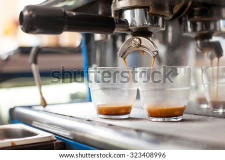 Close up of double shot espresso extraction into shot glasses