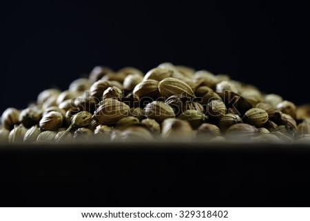 Close-up of dried coriander seeds in a wooden plate on a wooden table  - stock photo