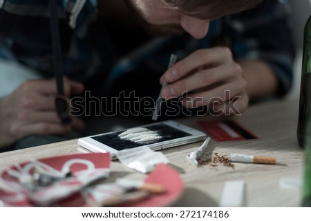 Close-up of drug addicted man taking cocaine - stock photo