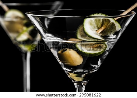 Close-up of dry martini with a lime slice and a green olive on a black background