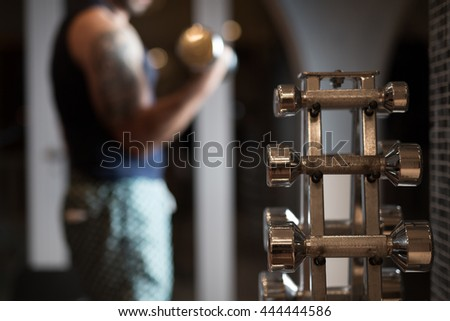 Close up of dumbbell. Strong muscular bodybuilder doing exercise with dumbbell in the gym. Part of fitness body.Sports and fitness.Fitness man in the gym. Strong man at the gym lifting weights.Low key - stock photo