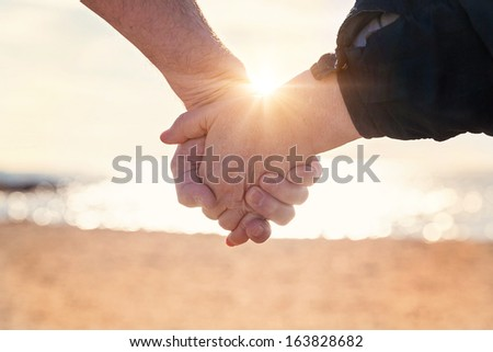 Close up of elderly couple holding hands on the beach at sunset - stock photo