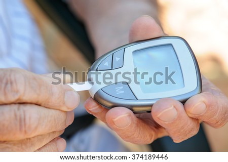 Close up of elderly man's hands measuring his blood sugar with a blood sugar monitor. This is one of a six picture series. In this picture he inserts the disposable test strip into the monitor  - stock photo