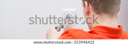 Close-up of electrician at work repairing outlet - stock photo