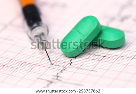 Close up of electrocardiograph with pills and syringe - stock photo