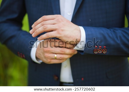 close-up of elegance male hands. man dressed in blue suit and white shirt standing over green nature background. groom or businessman - stock photo