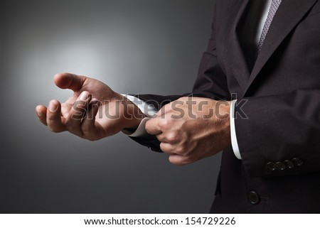 Close-up of elegance man hands with cufflink over dark background - stock photo