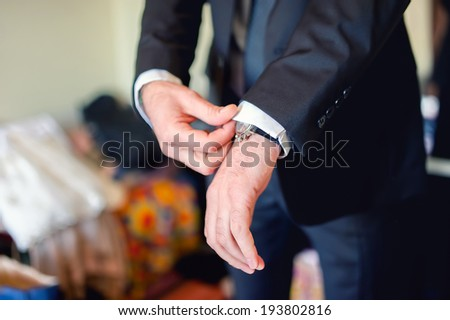 Close up of elegant man, groom hands with suits, ring, necktie and cuff links on wedding day