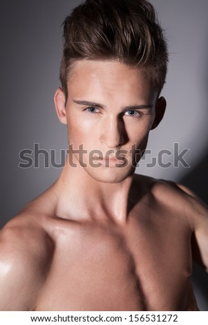 Close-up of elegant man with attractive face, stylish hairstyle and muscular torso, looking at camera