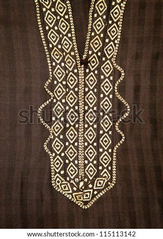 Close up of embroidered neck line on a black moroccan men's robe - stock photo