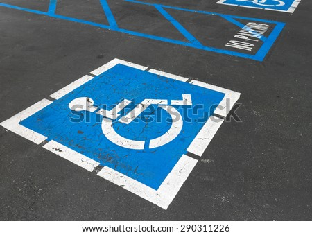 Close up of empty handicapped reserved parking space with wheelchair symbol on black asphalt. No parking white painted letters and blue diagonal lines in background. Rough cracked pavement.   - stock photo