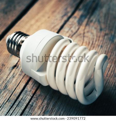 Close up of energy saving light bulb on wooden background. Vintage stylized. - stock photo