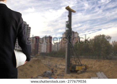 Close up of engineer hand holding white safety helmet for workers security standing in front of  blurred construction site in background - stock photo