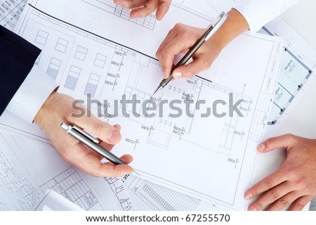 Close-up of engineers hands with pens over blueprints with sketches of projects